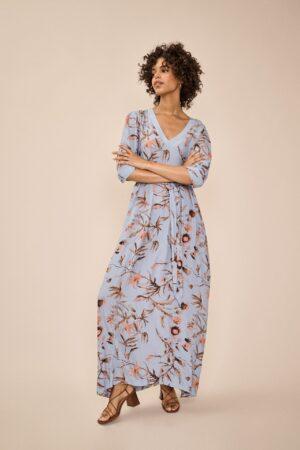 dziewczyna w długiej, niebieskiej sukienkce we wzór kwiatowy